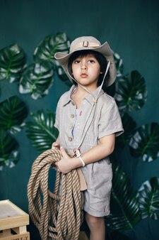 Chłopiec dziecko podróżnik w lniane ubrania trzymając linę stoi w studio