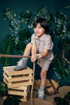Chłopiec dziecko podróżnik w lnianych ubraniach ciągnie linę stoi w studiu