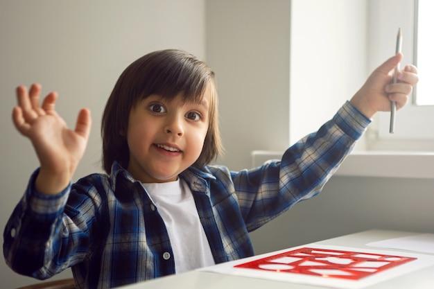 Chłopiec dziecko rysuje na papierze linijką na stole siedzącym przy oknie