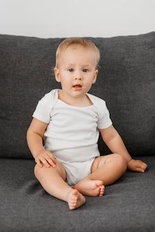 Chłopiec dziecko siedzi na kanapie, czekając do jedzenia