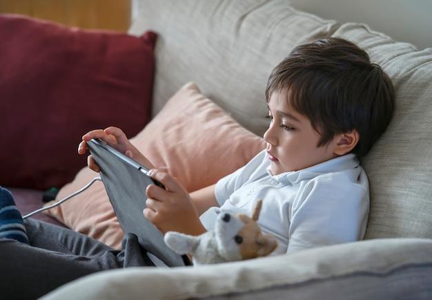 Chłopiec dziecko siedzi na kanapie oglądając bajki na telefonie komórkowym, dziecko w wieku szkolnym za pomocą telefonów komórkowych, ucząc się lekcji w internecie, nauka w domu, koncepcja edukacji online na odległość