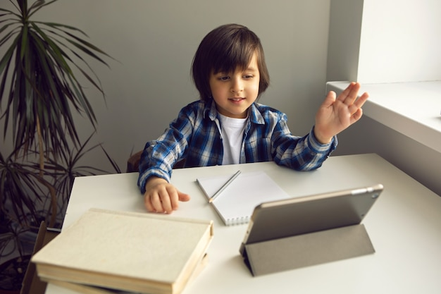 Chłopiec dziecko siedzi przy biurku i uczy się z notatnikiem tabletu i książką