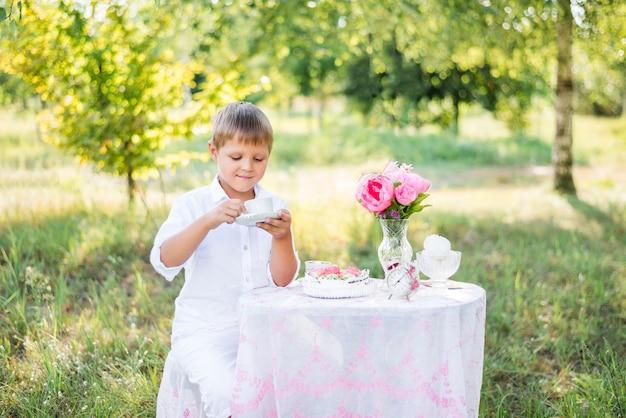 Chłopiec dziecko siedzi przy stole w przyrodzie. pijąc herbatę