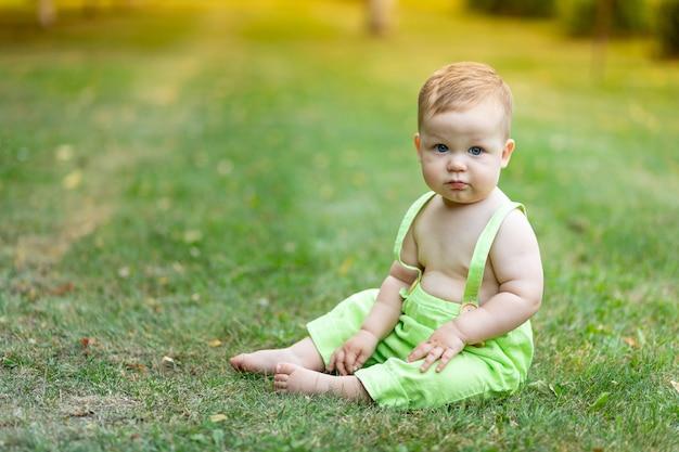 Chłopiec dziecko siedzieć na trawniku zielony latem, zdrowy spacer na świeżym powietrzu