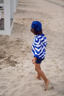 Chłopiec dziecko spacery po plaży z piaskiem na szezlongu w niebieskiej kurtce w paski i okularach przeciwsłonecznych