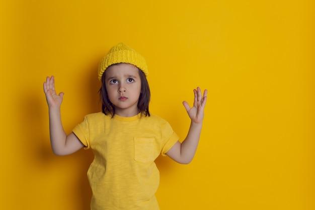 Chłopiec dziecko stoi przed żółtą ścianą w czapce z dzianiny