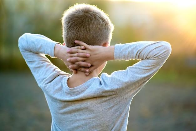 Chłopiec dziecko stojąc na zewnątrz w słoneczny letni dzień, ciesząc się ciepłą pogodą na zewnątrz.