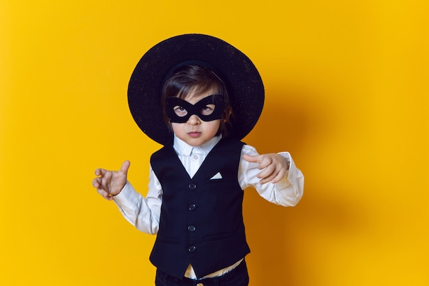 Chłopiec dziecko superbohater w garniturze i czarnej masce i kapeluszu na żółtej ścianie boso