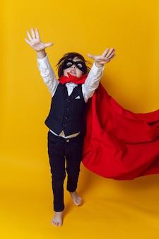 Chłopiec dziecko superbohater w garniturze i czarnej masce na żółtej ścianie boso