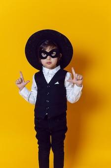 Chłopiec dziecko superbohater w garniturze i czarnej masce oraz pistolet na żółtej ścianie boso