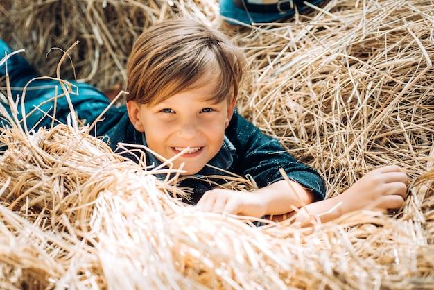 Chłopiec dziecko trzyma złoty liść i leży na sianie. do widzenia lato - cześć jesień. wyprzedaż na całą kolekcję jesienną
