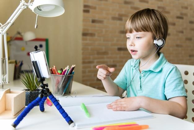 Chłopiec dziecko używa cyfrowego tabletu do rozmowy wideo ze swoim nauczycielem. ekran pokazuje wykład online. wyjaśnianie tematu z klasy. nauczanie domowe, nauczanie na odległość, nauczanie domowe. covid-19