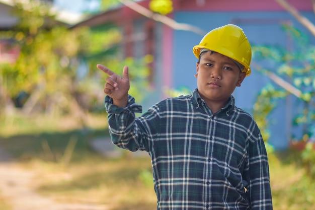 Chłopiec dziecko używać kask inżynier budowy