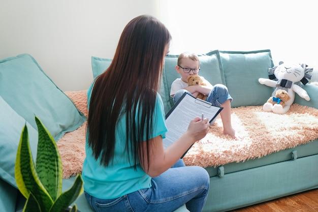 Chłopiec dziecko w biurze psychologów. psycholog rozmawia z dzieckiem, problemy studenckie