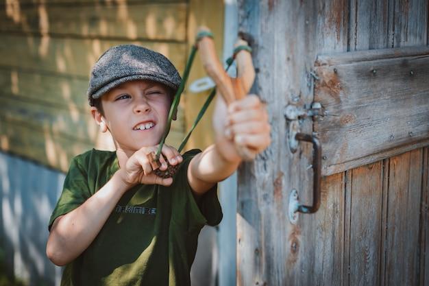 Chłopiec dziecko w czapce celuje z procy, aby strzelać do celu. pobaw się jako dziecko w wiosce na wakacjach.