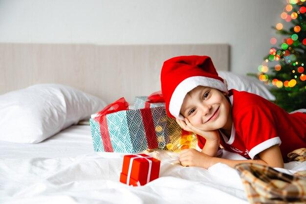 Chłopiec dziecko w czerwonym santa hat leży na łóżku z pudełkami z prezentami