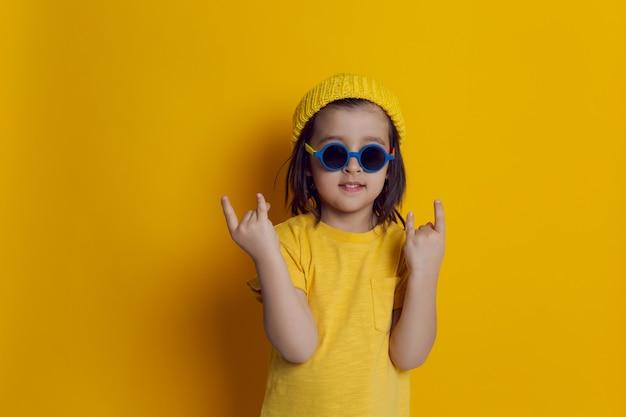 Chłopiec dziecko w kapeluszu i okrągłych okularach przeciwsłonecznych pokazuje znak rocka