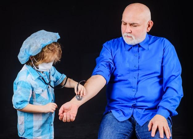 Chłopiec dziecko w masce medycznej z stetoskopem bawi się z dziadkiem u lekarza i pacjenta.