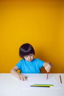 Chłopiec dziecko w niebieskiej koszulce na żółtej ścianie siedzi przy białym stole i rysuje kredkami