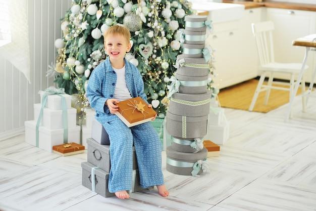 Chłopiec dziecko w niebieskiej piżamie siedzi na pudełkach z prezentami na tle choinki i stos prezentów.