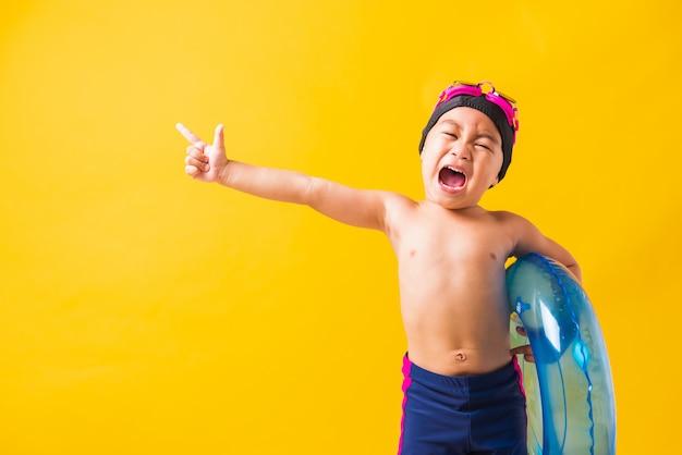 Chłopiec dziecko w okularach i strój kąpielowy gospodarstwa plaży niebieski nadmuchiwany pierścień