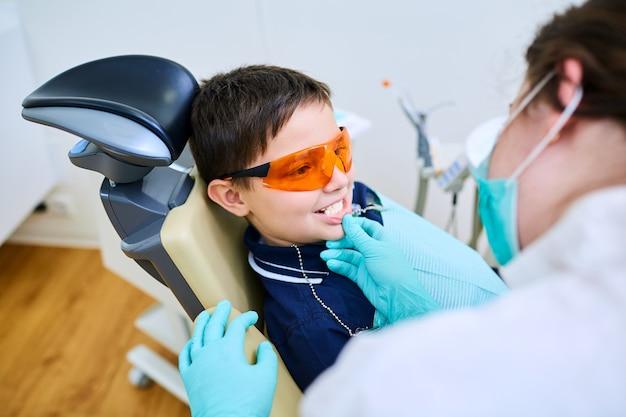 Chłopiec dziecko w pomarańczowych okularach ma dentystę