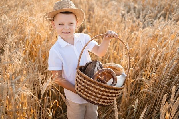 Chłopiec dziecko w słomkowym kapeluszu trzyma kosz chleba w polu pszenicy. ekologiczne produkty rolne.