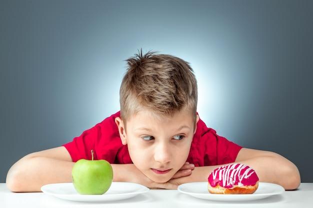 Chłopiec dziecko wybiera między pączkiem a zielonym jabłkiem. koncepcja odporność na pokusy, fast foody, zdrowe jedzenie, dieta.