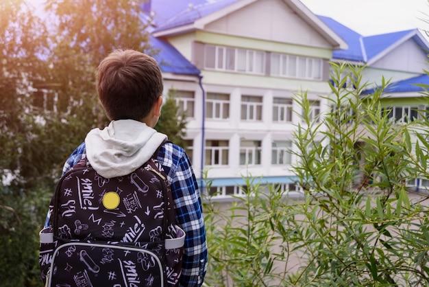 Chłopiec dziecko z torbą wygląda na szkołę podstawową. widok z tyłu