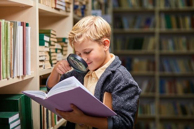 Chłopiec dziecko za pomocą lupy do czytania, uzyskać nowe informacje dla mózgu w bibliotece