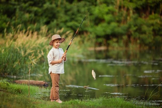 Chłopiec dziecko zajmujący się hobby. w lecie stoi na brzegu rzeki i trzyma wędkę z złapaną rybą