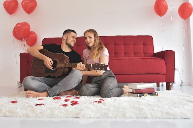 Chłopiec dziewczyna gra na gitarze w pokoju romantyczne szczęście w miłości walentynki