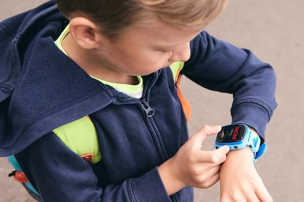 Chłopiec dzwoni do mamy ze smartwatchem dla dzieci