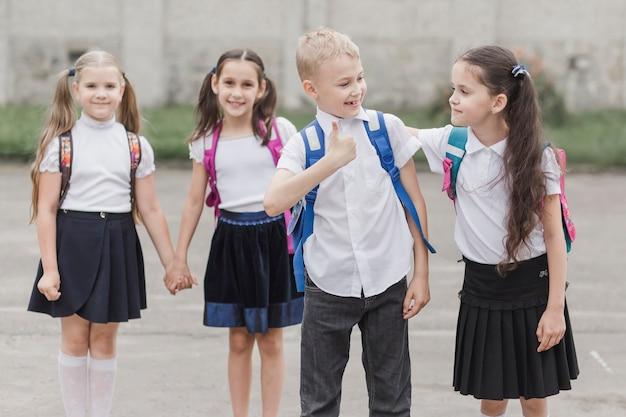 Chłopiec gestykuluje kciuk podczas gdy stojący blisko dziewczyny