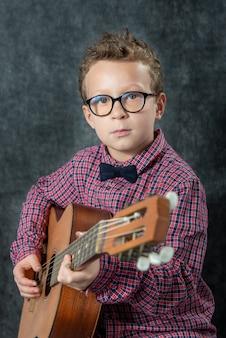 Chłopiec gra na gitarze akustycznej