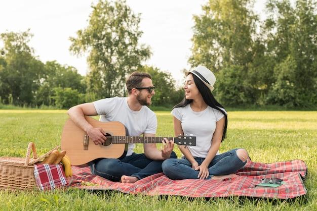 Chłopiec gra na gitarze dla swojej dziewczyny na koc piknikowy