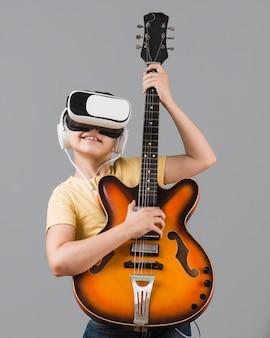 Chłopiec gra na gitarze podczas korzystania z zestawu słuchawkowego wirtualnej rzeczywistości
