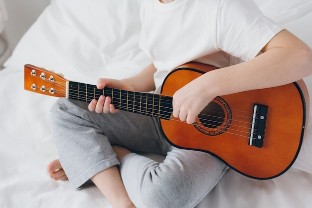 Chłopiec gra na małej gitarze, siedząc na łóżku