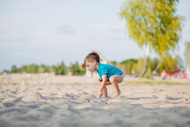 Chłopiec gra na plaży. zabawa dla dzieci na morzu na letnie rodzinne wakacje. zabawki do piasku i wody, ochrona przeciwsłoneczna dla małego dziecka. mały chłopiec kopanie piasku, budowanie zamku na brzegu oceanu.