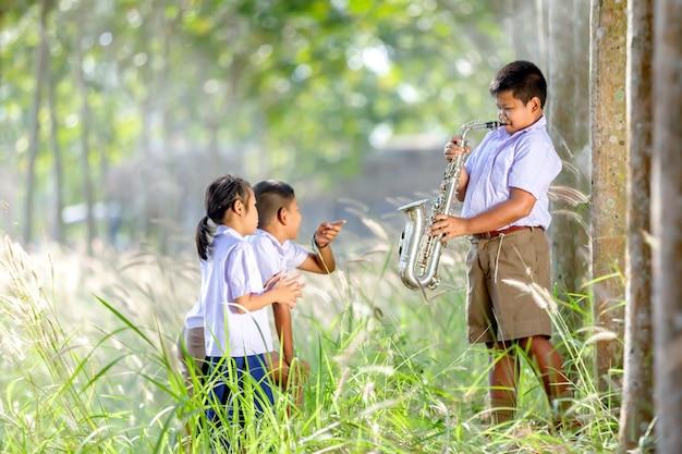 Chłopiec gra na saksofonie miłej zabawy słuchając przyjaciół.