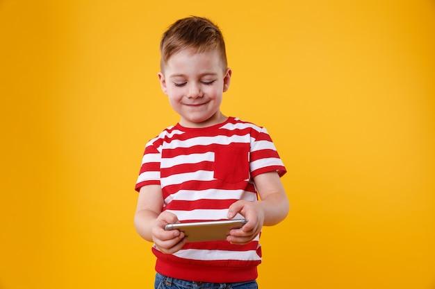 Chłopiec gra w gry lub surfuje po internecie na cyfrowy smartfon