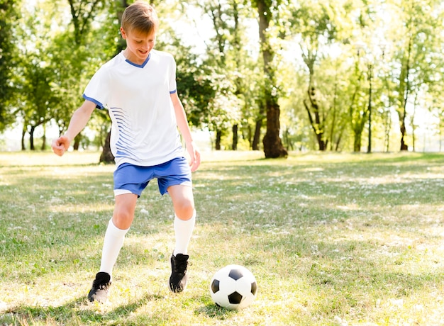 Chłopiec gra w piłkę nożną sam