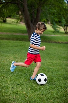 Chłopiec gra w piłkę nożną w parku