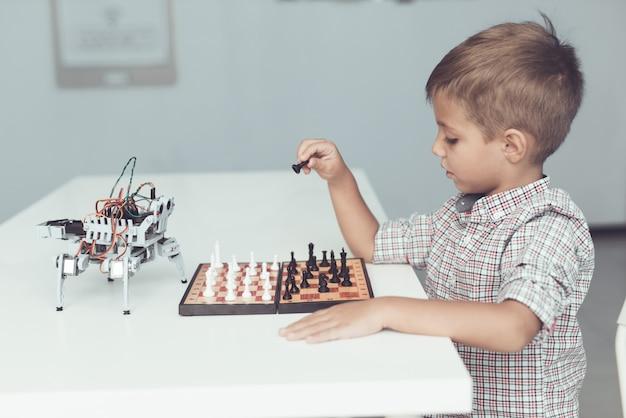 Chłopiec gra w szachy z małym robotem przy stole.