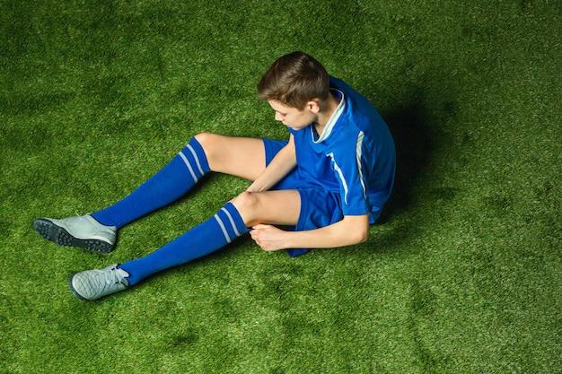 Chłopiec gracza piłki nożnej obsiadanie na zielonej trawie