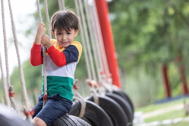 Chłopiec grający na huśtawce z oponami wiszący na placu zabaw i bawiący się zdrowymi letnimi wakacjami