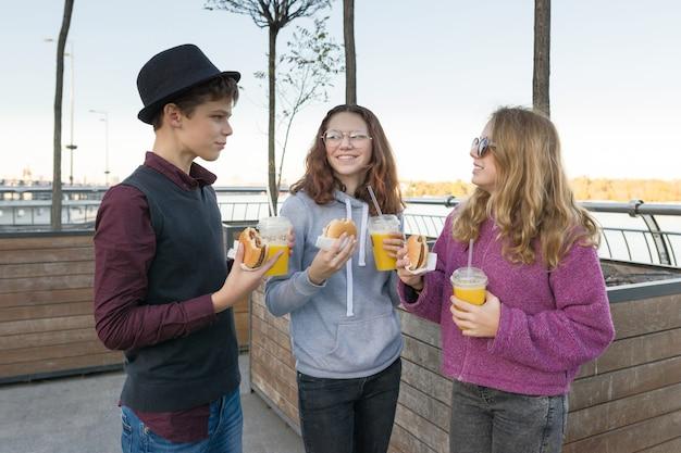 Chłopiec i dwie dziewczyny na ulicy miasta z burgerami i sokiem pomarańczowym
