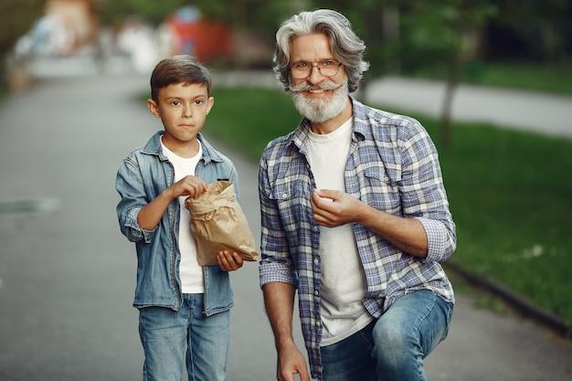 Chłopiec i dziadek spacerują po parku. stary człowiek gra z wnukiem. ludzie jedzą popcorn.
