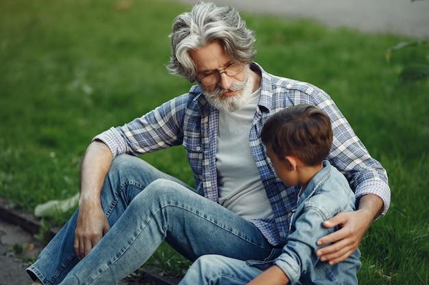 Chłopiec i dziadek spacerują po parku. stary człowiek gra z wnukiem. rodzina siedzi na trawie.
