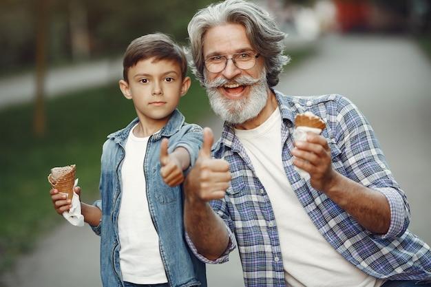Chłopiec i dziadek spacerują po parku. stary człowiek gra z wnukiem. rodzina z lodami.